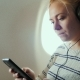 Young Attractive Woman Is Flying in an Airplane. It Uses a Smartphone Listening To Music - VideoHive Item for Sale