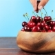 Man's Hand Take Red Cherries in Wooden Bowl on Wooden Table and Blue Background