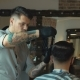 Barber with Dark Hair and Tattoo Wearing White Shirt and Black Gloves Doing a Haircut - VideoHive Item for Sale