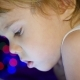 The Child Looks To the Tablet Lying on Bed. In the Background, Bokeh Lights and Garlands of - VideoHive Item for Sale