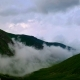 of Fog and Clouds Rolling Over Spring Mountain Green Valley in Kavkaz Region - VideoHive Item for Sale