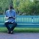 Man on Bench in Park Using a Tablet and Writing in Notepad - VideoHive Item for Sale