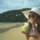 Girl Holding Fresh Cold Coconut At Tropical Beach - VideoHive Item for Sale