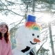 Winter Selfie, Cute Girl Making Photo with Snowman, a Mobile Phone in the Hand of Young Woman Making Nulled