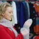 Attractive Woman in a Red Sweater Tries Warm Mittens. It Should Be in a Clothing Store - VideoHive Item for Sale
