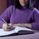 Young Woman Writes in Her Purple Notebook - VideoHive Item for Sale
