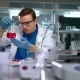 Researcher Analyzing Liquid in Glass Flask and Writing Data at Research Lab - VideoHive Item for Sale