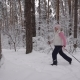 Elderly Woman Dressed in Winter Sport Clothes Quickly Goes on the Path Using Special Sticks for
