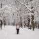 Elderly Woman Is Engaged in a New Type of Sports Walking in Winter Snow-covered Wood. Active Nulled
