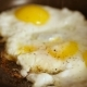 Cooking Fried Eggs with Spice in Frying Pan for Breakfast