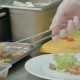 Chef's Hands Decorating Shrimp Salad on a White Plate
