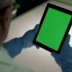 Scientist in Protective Rubber Gloves Is Using Tablet PC with Green Screen in Modern Laboratory on a