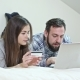 Happy Couple Using a Laptop Lying on a Bed at Home