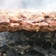 Cooking of Pig Meat on the Metal Skewers on Coals