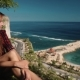 Young Woman Sitting on Edge of a Cliff Overlooking Roads and Ocean - VideoHive Item for Sale