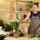 Beautiful Girl Florist, Salesman in a Flower Shop, She Unpacks Roses, Preparing Flowers for Making