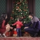 Young Family Sits Near the Rich Christmas Tree. It Is Decorated Garland, Toys, Ribbons, Bows. Mom