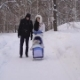 Winter Park. The Couple Spend Time with a Child in the Park. Woman in Warm Jacket Rolls the Stroller