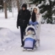 Young Beautiful Dressed Parents Walking on Snow-covered Park with Child