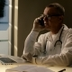Old Medical Consultant in Medical Gown with Stethoscope Giving an Advice By Mobile Cell Phone and