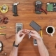 Man Repairing a Mobile Phone. Checks Parts Inside the Device. Wooden Table Top View. - VideoHive Item for Sale