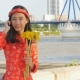 Beautiful Vietnamese Girl in Red Traditional Dress Ao Dai with Yellow Flowers