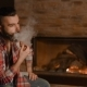 a Young Man with a Beard Smokes a Pipe in a Wooden House - VideoHive Item for Sale