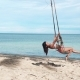 Sexy Woman Having Fun Swinging at Tropical Beach