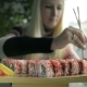 Girl Eating Sushi with Chopsticks in a Japanese Restaurant Focus on the Sushi - VideoHive Item for Sale
