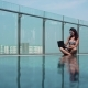 Woman Using Laptop in the Pool in Luxury Apartment