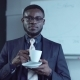 Cheerful African American Businessman Having a Hot Drink