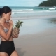 Happy Girl Holding a Pinapple Cocktail on a Beach
