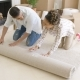 Young Couple Rolling Up a Rug As They Move House - VideoHive Item for Sale