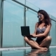 Woman Using Laptop in the Pool on a Sunny Day
