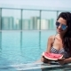 Young Sexy Girl Eating Watermelon in the Pool