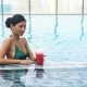 Young Pretty Sexy Girl Drinking Cocktail in Pool
