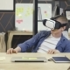 Young Man Uses Virtual Reality Glasses in Office