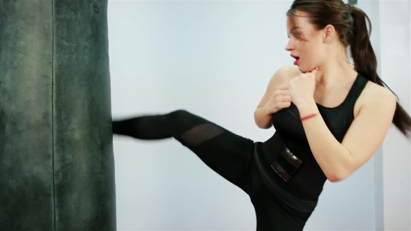 Beautiful Brunette Boxing Pear, Beautiful Kickboxing Woman Training Punching Bag in Fitness Studio