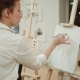 Female Painter Drawing in Art Studio Using Easel