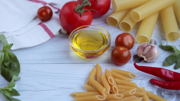 Olive Oil, Tomatos, Basil and Diffrent Kinds of Pasta on White Wooden Table