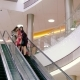 Beautiful Young Women in Shopping Mall Moving Down on Escalator To Continue Their Shopping - VideoHive Item for Sale
