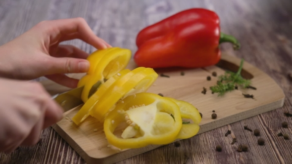 Woman Hands Cuts Pepper on a Wooden Table