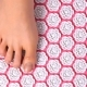 Female Feet Gently Tread on Acupuncture Massage Mat. Top View.