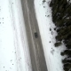 Aerial Tilt Up of Car Driving on Winter Road in Mountains During Snow Storm