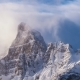 Clouds Flowing Over Snowy Mountain Peak at Sunrise