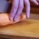 Woman Hands with a Knife Sliced Carrot with Knife on a Wooden Kitchen Board in a Home Kitchen