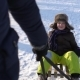 Dad Rolls His Son on a Sled. Boy Smiling Happily. Cold Sunny Day.