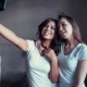 Beautyful Smiling Girls in White T-shirt Grimace and Make Selfie Using Smartphone.