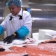 Asian Man Slicing a Fillet of Salmon at Table in a Fish Shop