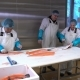 Workers Slicing a Fillet of Salmon at Table on the Fish Factory